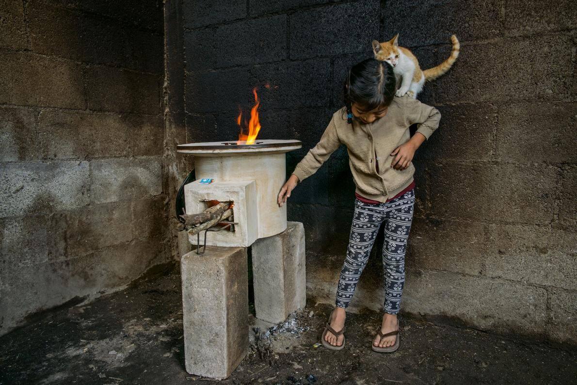 Таня Лопес, грає з котою в кімнаті, стіни якої були обпалені вогнем; нова піч, надана StoveTeam International, ефективна і безпечна для дотику.